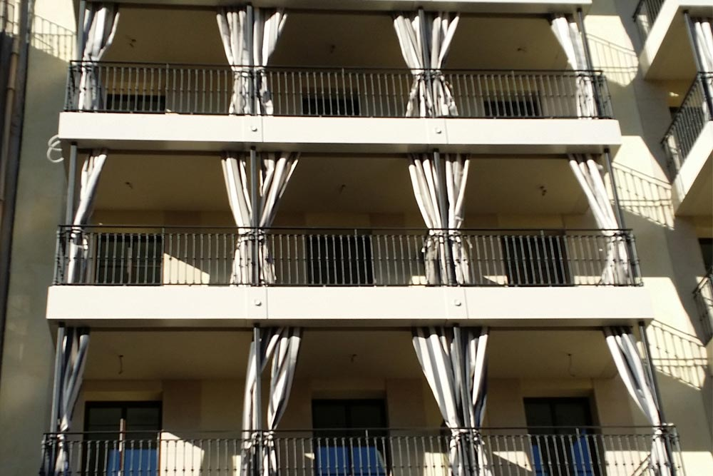 Terraces in facade of building with curtain awning niagara