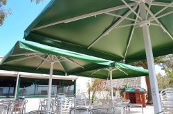 Three Azores parasols with green canvas and white mast.