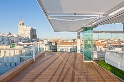 Awning Cofre Light on a roof terrace with views of Madrid
