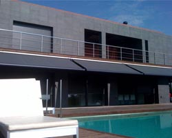 Three awnings ma mx990 black in line in terrace with swimming pool