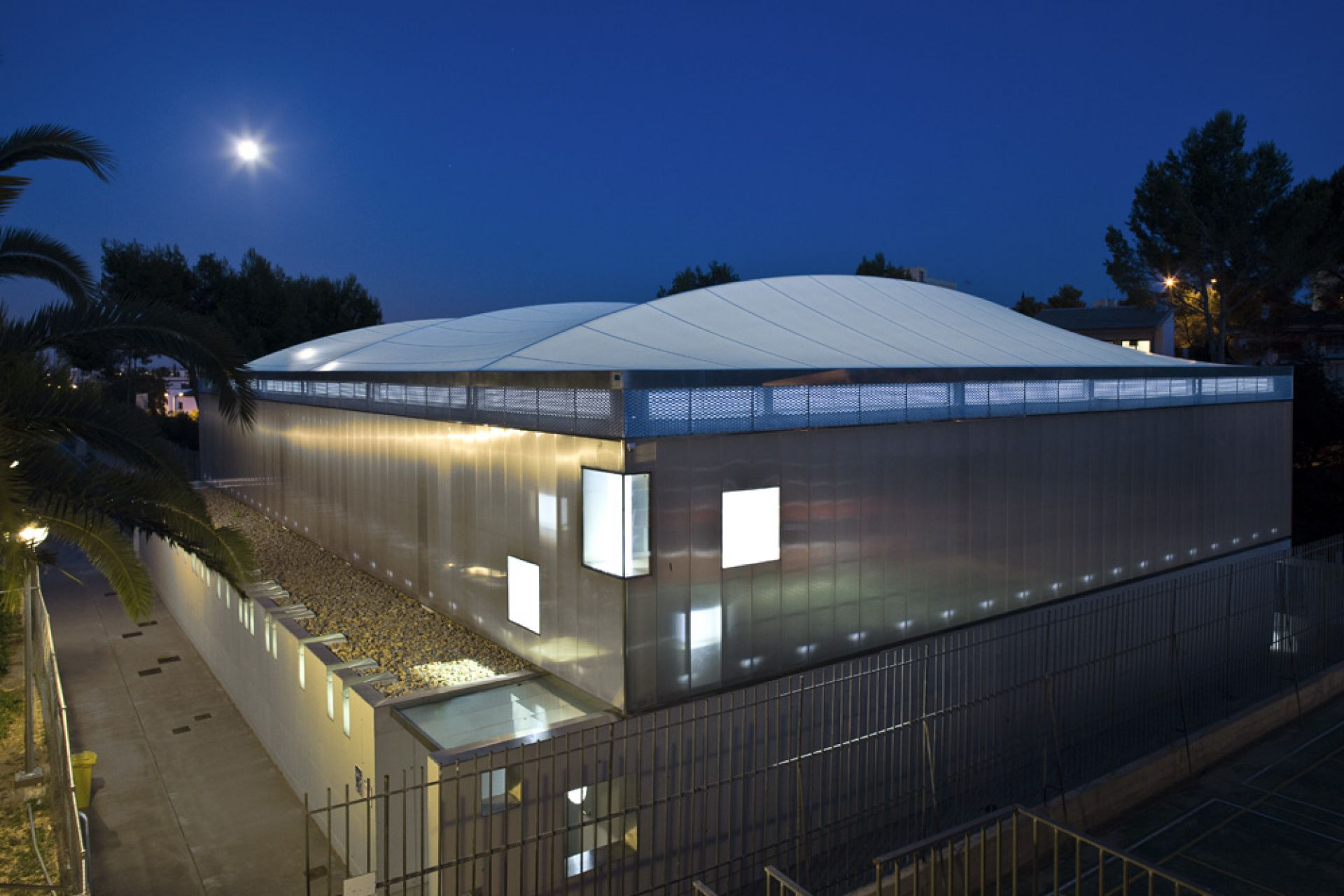night image of the exterior of the sports center cover