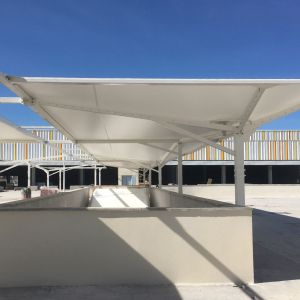 Parking canopies made with tensioned membranes.
